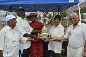 USACUA's Fitzroy Hayles receiving the Trophy from the wife & son of Jerry Kishun. Krish Prasad on right.